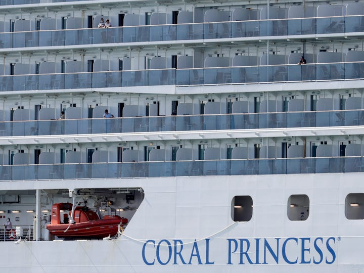 People look out from their balconies on the Coral Princess cruise ship as it is docked at PortMiami on April 4, 2020.