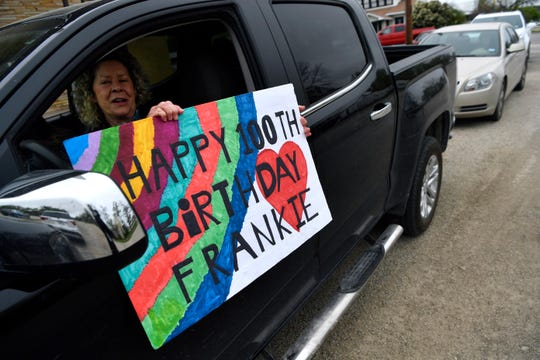 Janie Benson holds a sign out her truck's window celebrating Frankie Sprouse's 100th birthday Friday in Baird