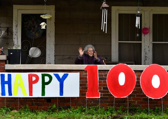"""Frankie Sprouse claps her hands and waves at the cars driving by as they celebrate her 100th birthday in Baird Friday by honking their horns and waving signs. Coronavirus concerns kept the community from holding a traditional party, opting instead for the """"birthday honk."""""""