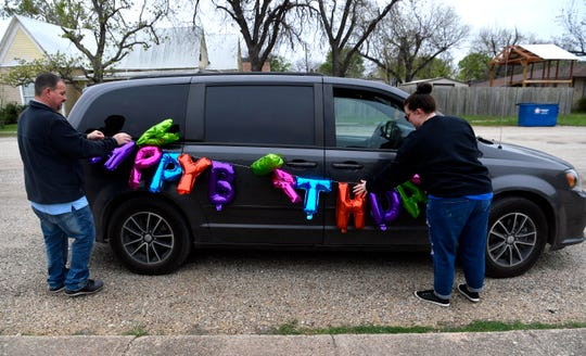 """Ryan and Dana Ward tie to their minivan a string of balloon letters spelling """"Happy Birthday"""" in Baird Friday."""