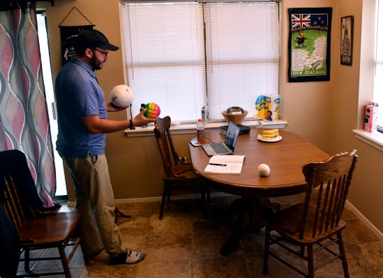 Greg Zietlow, a third grade teacher at Austin Elementary School, teaches a lesson over Zoom on the phases of the moon using balls during the first week of social distancing March 18. Zietlow uses the teleconferencing software to connect weekly with his students.