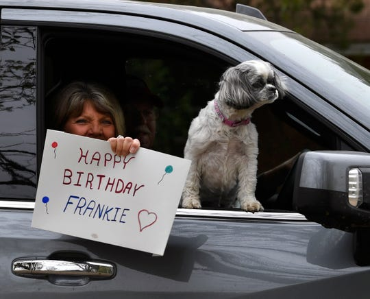A woman holds a sign wishing Frankie Sprouse well on her 100th birthday in Baird Friday.