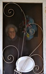 Frankie Sprouse stands behind her screen door Friday on her 100th birthday.