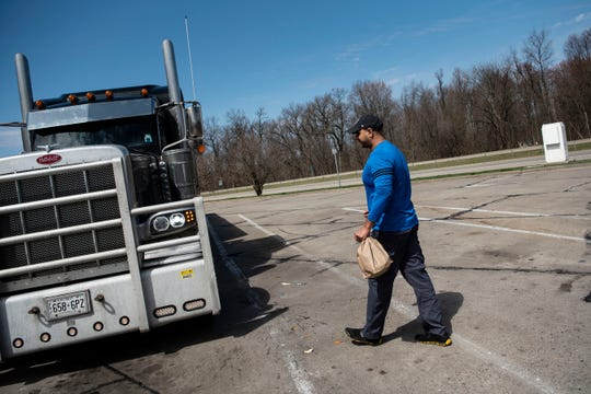 Sonny Singh, owner of Hogzilla BBQ Smokehouse And Bar, gives Ontario truck driver Gurpreet Singh Jandir a care package on Sunday, April 5, 2020 at Exit 97 Rest Area in Battle Creek, Mich. Packages include hand sanitizer, gloves, snacks and water.