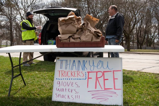 Sonny Singh, owner of Hogzilla BBQ Smokehouse And Bar, gives Los Angeles truck driver Jerry Hernandez a care package on Sunday, April 5, 2020 at Exit 97 Rest Area in Battle Creek, Mich. Packages include hand sanitizer, gloves, snacks and water.