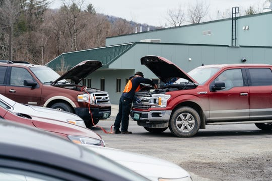Jeremy Ciampi helps jump start a truck battery after a drive-in church service in Randolph on April 5, 2020. At least four vehicles in the congregation of nearly 100 needed a jump after listening to the hourlong service on the radio.