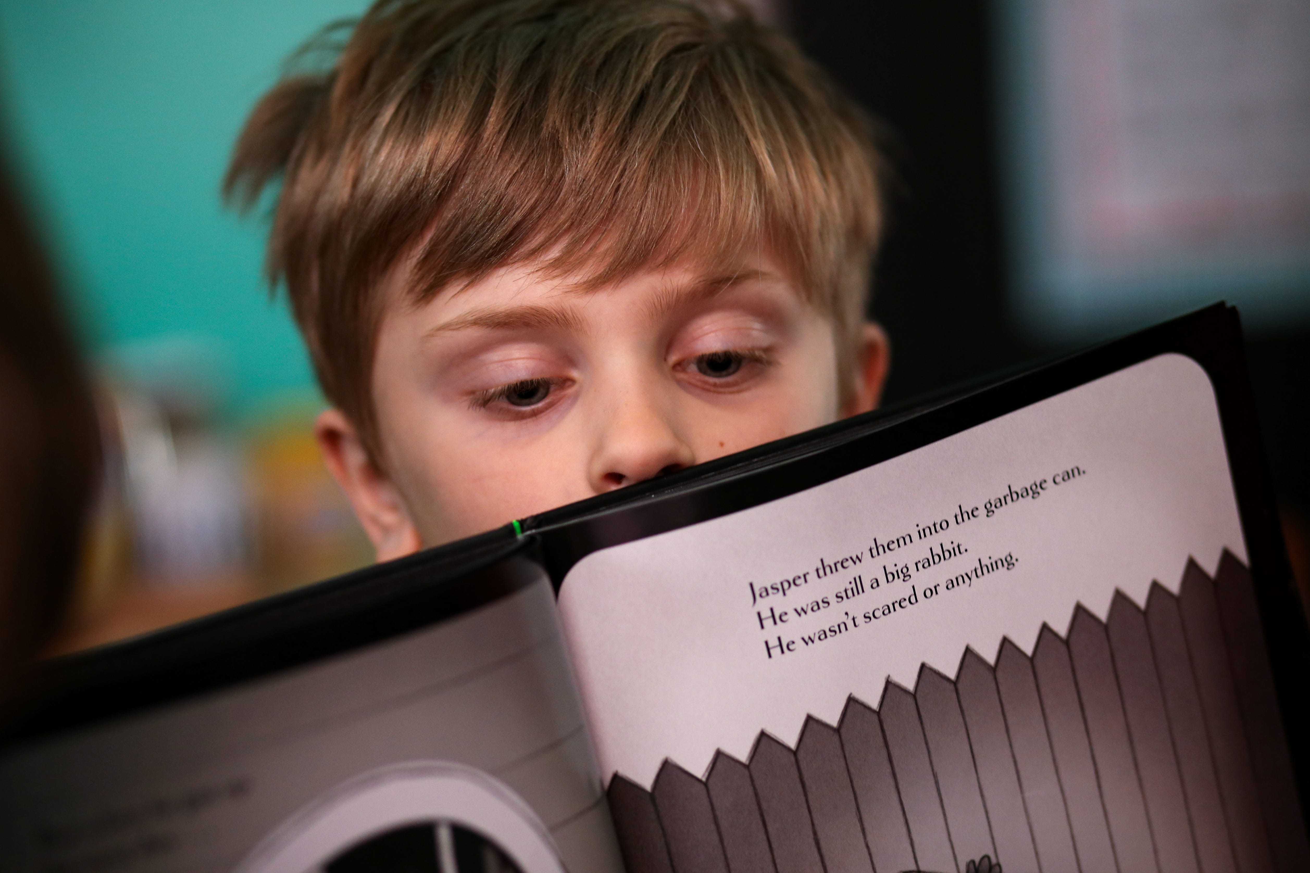 Tommy Minelli, 6, peers over the edge of a book during a video conference call, Thursday, April 2, 2020, in Cincinnati's Northside neighborhood. About a dozen of his mother's colleagues get together and rotate teaching their kids a lesson from a range of subjects.