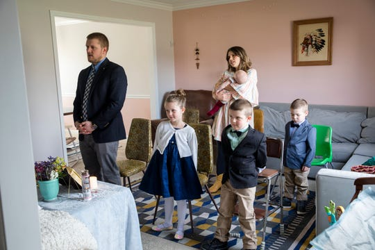 Glenn and Lara Gigandet watch a live streamed Mass with their children Dorothy, 6, Charles, 5, Paul, 3, and Mabel, five-month-old, on Sunday, March 22, 2020 at their home in Mason. The Archdiocese of Cincinnati suspended all public Masses due to the new coronavirus pandemic.