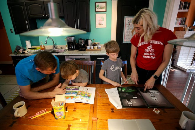 Mark Minelli, left, works with his son, Nico, 3, while Emily Minelli works with their oldest son, Tommy, 6, right, Thursday, April 2, 2020, in Cincinnati's Northside neighborhood. Emily and her husband Mark spend their weekdays switching between their full-time responsibilities as parents and workers plus his studies in graduate school.