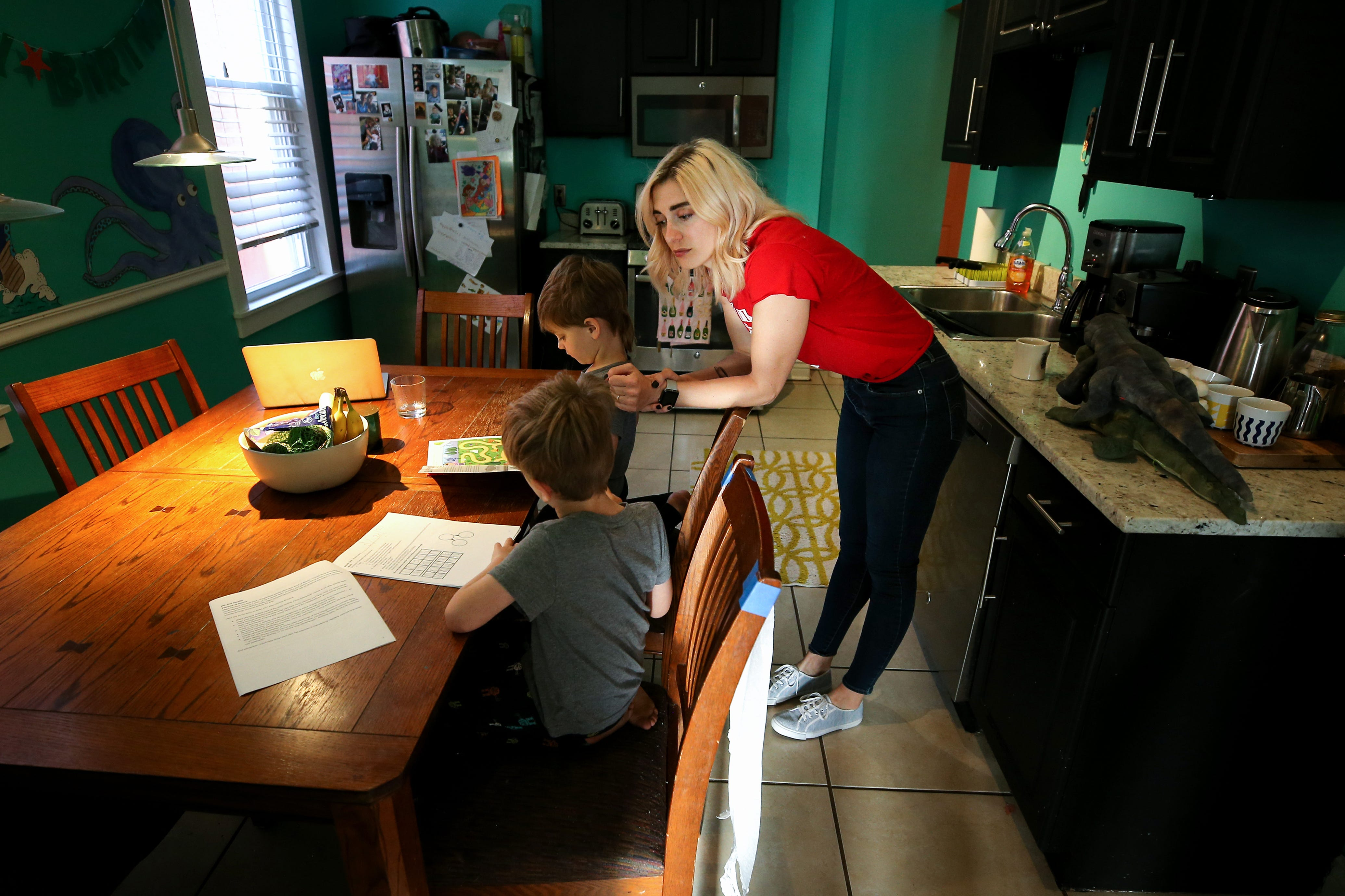 Emily Minelli, a Princeton High School French teacher, begins the day with educational work with her two sons, Nico, 3, top, and Tommy, 6, bottom, Thursday, April 2, 2020, in Cincinnati's Northside neighborhood