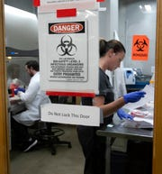 Laboratory Technologist Roger Knauf, left, and Sarah Dell, test for COVID-19, the illness caused by the new coronavirus at Gravity Diagnostics in Covington, Kentucky Tuesday, March 24, 2020. The work is conducted in a secure area and the actual test is done behind glass. The lab was founded in 2014 and was approved for COVID-19 testing on March 16. The CEO is Tony Remington.