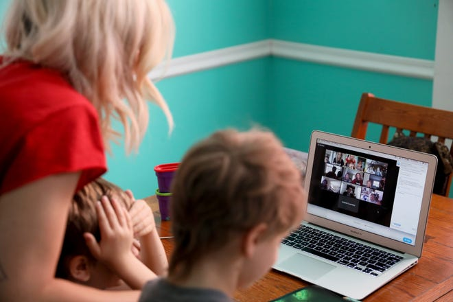 Emily Minelli and her two sons Nico, 3, left, and Tommy, 6, right, log onto a video conference call, Thursday, April 2, 2020, in Cincinnati's Northside neighborhood. About a dozen of Emily's colleagues get together and rotate teaching their kids a lesson from a range of subjects. It was Emily's turn.