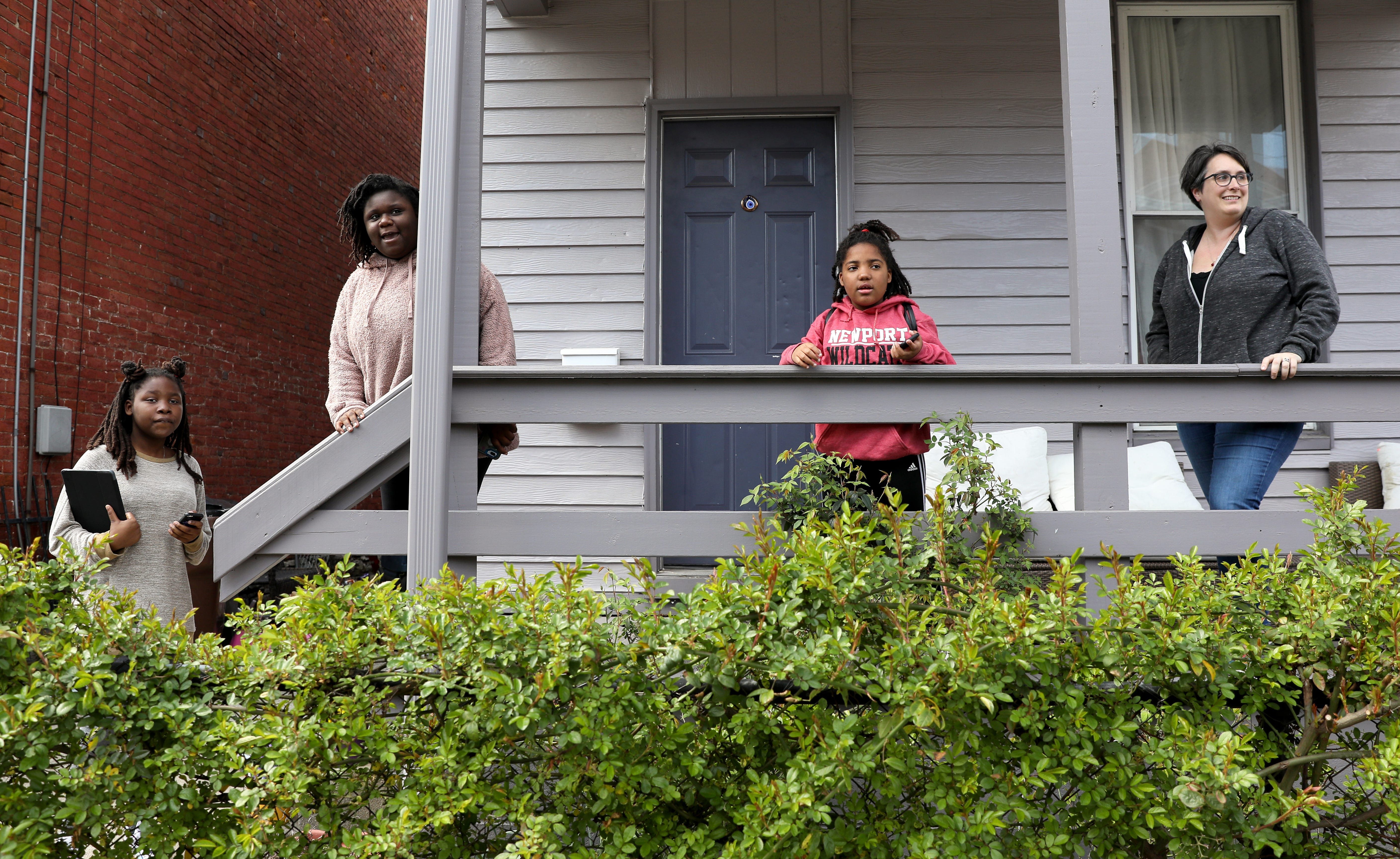 From left: Haddasha Revely-Curtin, 12, Christy Revely-Curtin, 13, Zionnah Revely-Curtin, 7, and Rose Curtin, spot a neighborhood on Columbia Street, Thursday, April 2, 2020, in Newport Ky.
