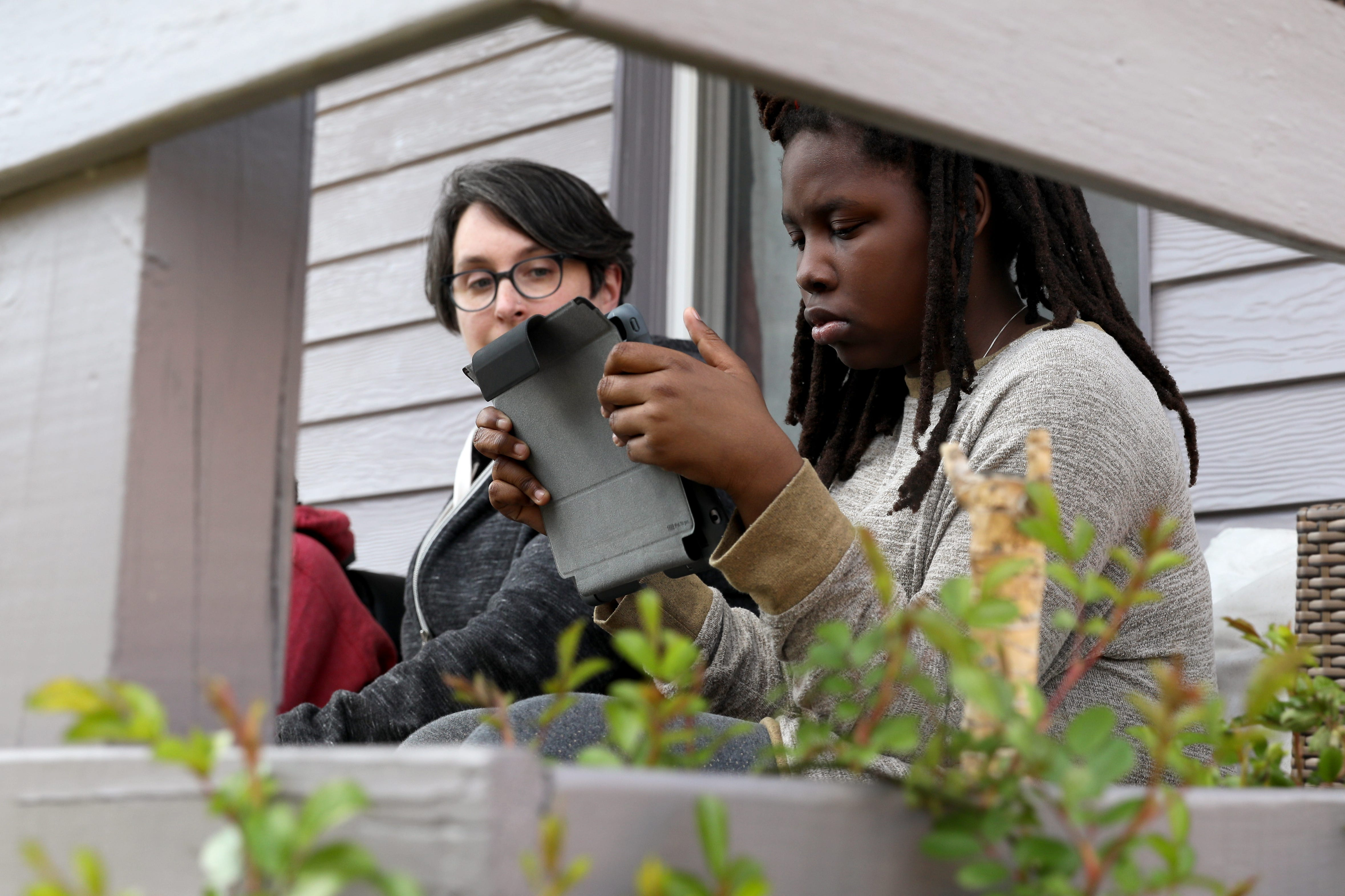 Rose Curtin, left, looks over Haddasha Revely-Curtin's shoulder while she does school work, Thursday, April 2, 2020, in Newport, Ky. Incoming seventh-grader Haddasha, age 12, had battled anxiety at the start of the pandemic, which is one reason Curtin decided to keep her three children home when school starts this fall.