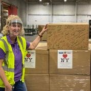 Kristina Karschnia, vice president of manufacturing and operations at Troy Design and Manufacturing, stands behind the 1 millionth face shield in a box that was part of a shipment to New York.