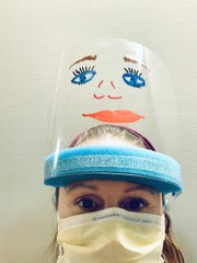 Sparrow Hospital nurse Katie Pontifex, 37, tries to ease the tension of working with COVID-19 patients by using dry-erase markers to decorate her face shield.