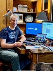 Adrian Price, director of global core engineering for vehicle manufacturing at Ford Motor Co., plays a key role on the company's COVID-19 task force. A face shield like the kind Ford makes for first responders is hanging behind him on the wall. Price is pictured here Sunday working from his Grosse Pointe Farms home.
