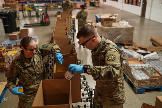 Michigan National Guard members PVT Kelsey Schruben and PFC Jacob Nachazel fill emergency food boxes at the Food Bank of Eastern Michigan Hunger Solution Center in Flint on Tuesday, March 31, 2020. The National Guard members are helping at several of the Food Bank Council of Michigan's seven regional food banks to cover fewer volunteers due to the stay-at-home executive order. The boxes, that feed 2-4 people, are to be distributed to 22 counties for drive-thru pickup.