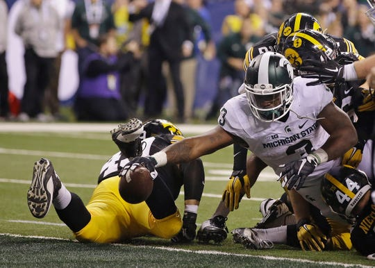 Michigan State's LJ Scott reaches the ball across the goal line in the 2015 Big Ten championship game.