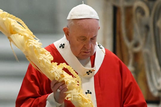 Pope Francis holds a palm branch as he celebrates Palm Sunday Mass behind closed doors in St. Peter's Basilica, at the Vatican, Sunday, April 5, 2020.