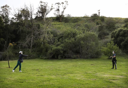LOS ANGELES, CALIFORNIA - APRIL 04: People play catch wearing face masks in Elysian Park amid the coronavirus pandemic on April 4, 2020 in Los Angeles, California. The U.S. COVID-19 death toll has now surpassed 8,000. (Photo by Mario Tama/Getty Images)