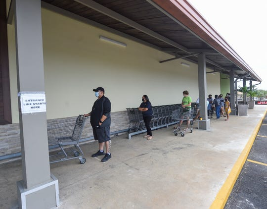 Customers line up outside Pay-Less Supermarkets in Maite in this April 5 file photo. A total of 500 checks have been sent so far for thePrugråman Salåppe' Ayudon I Taotao, totaling$365,000