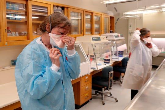 Cindy Morris, left, and Swarnamala Ratnayaka don personal protective equipment before the preparing RNA for testing for the new coronavirus at the molecular pathology lab at Tulane University School of Medicine in New Orleans, Thursday, April 2, 2020. AP Photo/Gerald Herbert)
