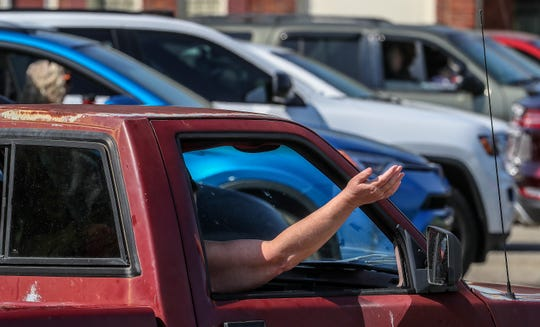 Churchgoers stayed in their cars as they listened to the message preached by Ed Tyler at Harvest Church of God on Sunday morning, April 5, 2020.  Toler preached from the back of a pickup truck in the parking lot of the church in Louisville's south end.  Each car had an open parking space next to it.