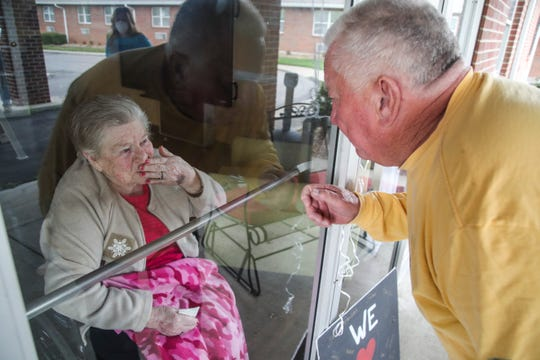Carl Perkins touches the glass as his mother Frances Perkins, 96, reacts during a birthday visit at Wesley Manor retirement center in Okolona Saturday morning. Perkins' daughter Norma Higgins helped organize the birthday visit. Last year, the family brought 95 roses for Perkins; however due to the coronavirus outbreak no visitors have been allowed inside for several weeks. April 4, 2020