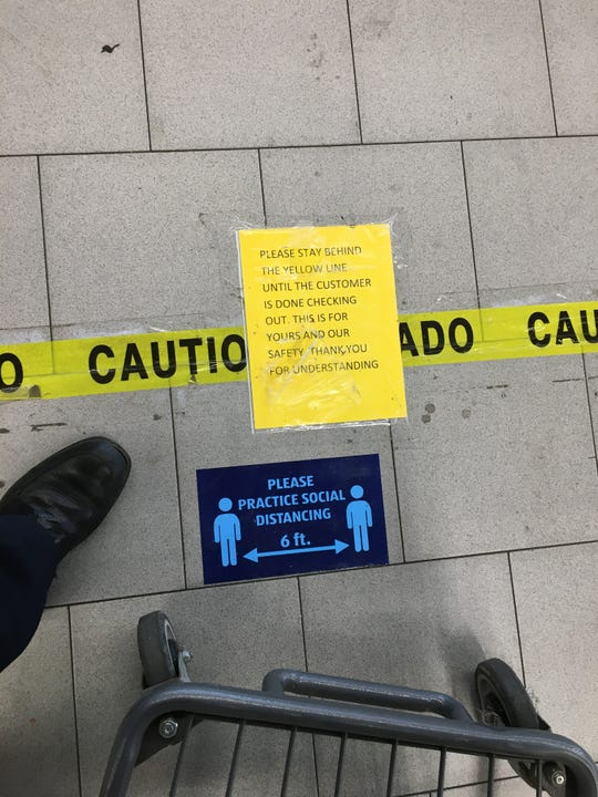 Saturday, April 4, 2020. A sign on the floor at the checkout line at the Aldi grocery store on Summer Avenue warned customers to stay apart from one another.
