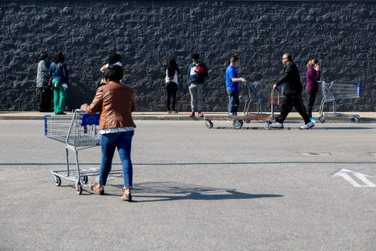 Customers leave space between each other as they line up along the building Sunday, April 5, 2020, at Sam's Club on Winchester Road in Memphis.