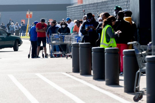 Customers line up along the building Sunday, April 5, 2020, at Sam's Club on Winchester Road in Memphis.