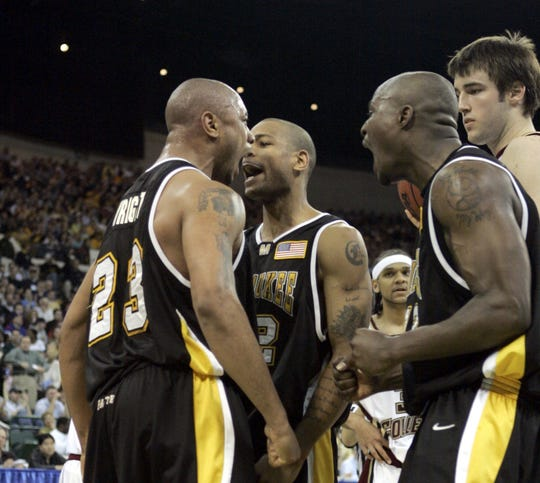 James Wright, left, celebrates with UWM teammates Ed McCants, center, and Joah Tucker after scoring and drawing a foul in the Panthers' win over Boston College that sent them to the  2005 Sweet 16.