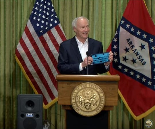 Gov. Asa Hutchinson, speaking at his Sunday news conference, holds a cloth mask that he wore out in public earlier that day.