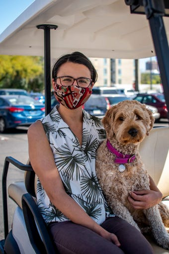 Desi Stoyanova and her dog Lucy sit for a portrait outside Safeway in Phoenix on April 4, 2020. A friend gave her the homemade mask.