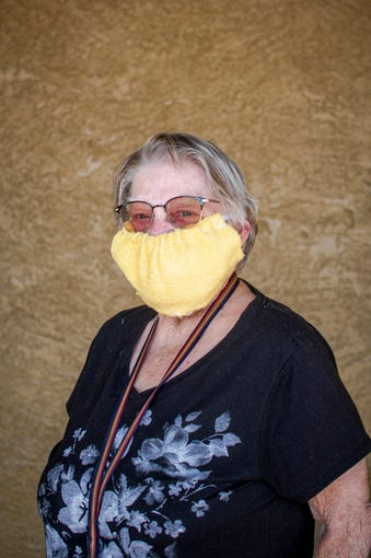 Nancy Walthper stands for a portrait outside Safeway in Phoenix on April 4, 2020. Her mask is made from a wash cloth.