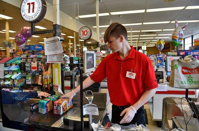 Cashier Brady Cummings rings up a customers groceries from behind a newly installed sneeze shield at Weis Markets, 2400 E. Market Street, Sunday, April 5, 2020.John A. Pavoncello photo