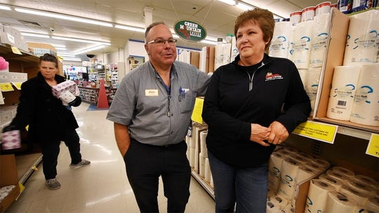 A shopper grabs items behind Greg, left, and Betti Saubel who have worked long hours keeping their four Saubel's Market stores stocked amid panic buying.
