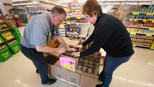 Greg, left, and Betti Saubel unpack Faber sanitizer they sourced from a local distillery after normal sources for product dried up at their Shrewsbury store. The Saubels have worked long hours keeping their five Saubel's Market stores stocked amid panic buying.