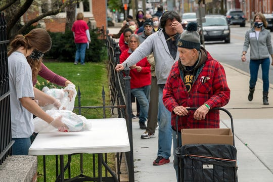Masked volunteers hand out meals to people waiting 6 feet apart in line at the First Presbyterian Church of York during the Community Take Away Dinner on Palm Sunday at the church in the 200 block of East Market Street. Churches have a variety of plans for Easter Sunday.