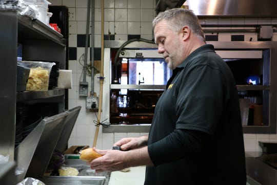 "Douglas ""Buxy"" Buxbaum makes a cheesesteak in the kitchen of Buxy's Salty Dog Saloon, a restaurant he's owned for 21 years in Ocean City. Buxbaum spent many late nights as a cook early on in his career, now he usually steers clear of the grill."
