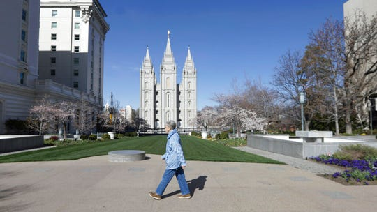 A woman walks past the Salt Lake Temple at Temple Square during The Church of Jesus Christ of Latter-day Saints' twice-annual church conference Saturday, April 4, 2020, in Salt Lake City.The twice-annual conference kicked off Saturday without anyone attending in person and top leaders sitting some 6 feet apart inside an empty room viewed via live-stream as the faith takes precautions to avoid the spread of the coronavirus. It is the first conference without a crowd since World War II, when wartime travel restrictions were in place. (AP Photo/Rick Bowmer)