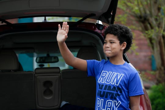 Hayden Reed waves to friends and family who gathered for a parade through his Crawfordville neighborhood to celebrate his 12th birthday Sunday, April 5, 2020.