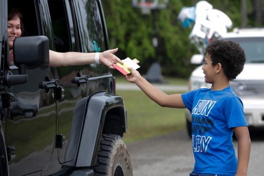 Hayden Reed gets a birthday card from his 12th birthday party parade in his Crawfordville neighborhood Sunday, April 5, 2020.