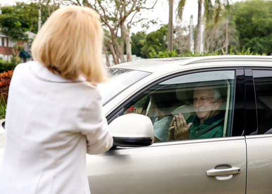"""Gary Zell (right), of Vero Beach, exchanges a sign of peace with Rev. Dr. Anna V. Copeland during the drive-thru palms and prayer event in the Community Church of Vero Beach parking lot on Palm Sunday, April 5, 2020, in Vero Beach. Because of the coronavirus pandemic, the church congregation has not been able to worship together inside of the church. """"The church isn't about the building,"""" said Rev. Copeland, the interim senior minister. """"It's about what people do to exercise compassion in the world, so the message is about what can we do to be the church and to love our neighbor even if we don't leave our living room."""" A palm cross and a prayer was placed under the windshield wiper of each car."""