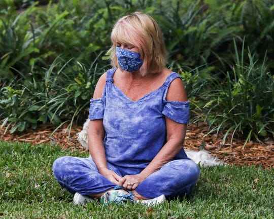 """Sarah Huff, of Vero Beach, becomes emotional as she watches a drive-thru palms and prayer event in the Community Church of Vero Beach parking lot on Palm Sunday, April 5, 2020, in Vero Beach. Because of the coronavirus pandemic, the church congregation has not been able to worship together inside of the church. After receiving a palm and prayer, Huff pulled her car over and sat across the street. """"I don't want to go anywhere, I don't want to be anywhere, I need to just be right here and feel,"""" said Huff. """"To feel their sense of support. It all just hit me like a brick."""""""