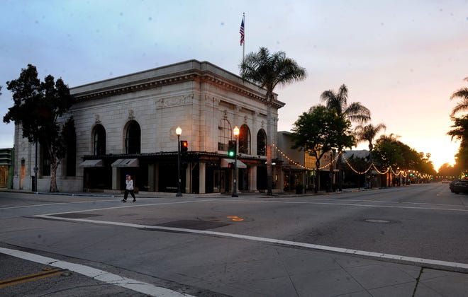 People walk near the Bank of Italy building on Main Street in downtown Ventura on Saturday, April 4, 2020.