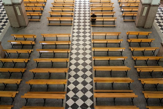 A Catholic priest sits on an empty bench due to social distancing guidelines during the coronavirus outbreak inside the Jesus de Medinaceli church on Palm Sunday in Madrid, Spain, Sunday, April 5, 2020.