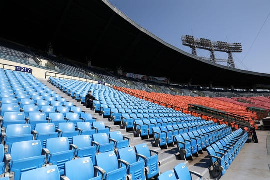 An employee of LG Twins watches an intrasquad game at an empty Jamsil baseball stadium on April 5.