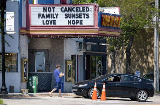 A customer leaves Vagabond Coffee on Edgewood Avenue with his takeout order as the marque on the Murray Hill Theater offered positive words in light of the closings around Jacksonville, Fla and the rest of the country in the effort to slow down the spread of the coronavirus Saturday, April 4, 2020.